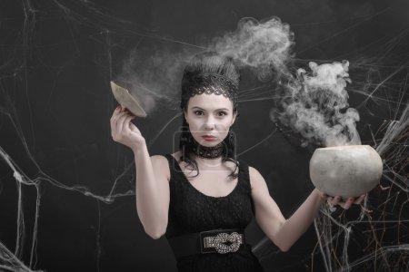 Photo pour Belle jeune fille dans l'image d'une sorcière prépare une potion magique. Costume de carnaval pour Halloween - image libre de droit