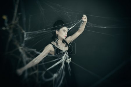 Photo for Beautiful young brunette in the image of the evil witch. A costume party on Halloween - Royalty Free Image