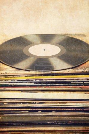 Photo pour Disque vinyle avec étiquette blanche sur le dessus d'une grande tour de pochettes d'album colorées, fond texturé, format portrait, reflets lumineux sur lp , - image libre de droit