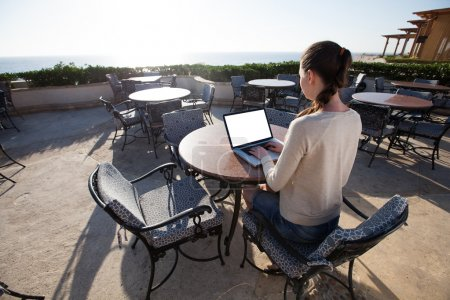 businesswoman typing on her laptop with sunflare on the resort
