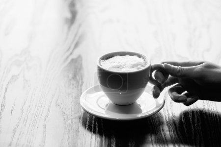 woman hands holding mug of hot coffee cup that standing on woode