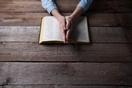 Photo pour Mains de femme priant avec une bible dans l'obscurité sur une table en bois - image libre de droit