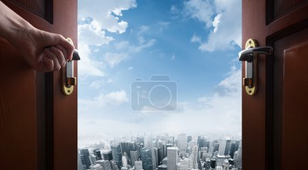 Photo for Hand opens room door to the city - Royalty Free Image