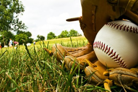 baseball and old baseball glove lying on the e on a baseball fi