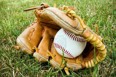 a baseball and an old baseball glove