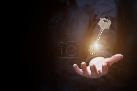 Business woman holding shining key in dark...