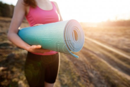 Woman walking with a yoga mat outside during sunse...