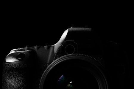 Photo pour Image d'une image moderne professionnelle de caméra de Dslr basse-clé - appareil-photo moderne d'escompte dans un espace foncé. La partie supérieure d'une caméra est visible et le reste va dans l'ombre - image libre de droit