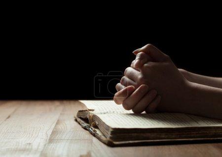 Photo pour Femme mains sur la bible. elle lit et prie au-dessus de la Bible dans un espace sombre au-dessus de la table en bois - image libre de droit