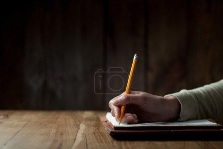 Photo pour Gros plan de la main de la femme écrivant sur du papier sur une table en bois - image libre de droit