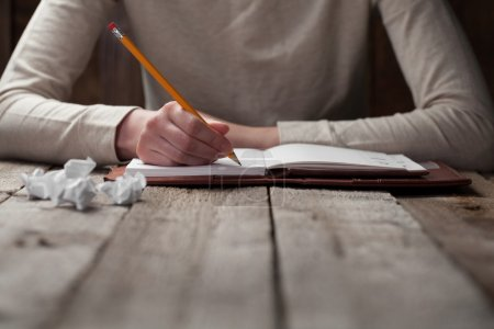 Photo for Hand writes with a pen in a notebook - Royalty Free Image