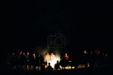 Photo pour Les gens s'assoient la nuit autour d'un feu de joie lumineux. floue - image libre de droit