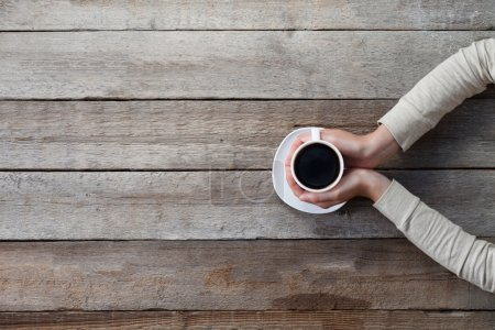 Photo for Woman hands holding mug of hot coffe cup that standing on wooden table - Royalty Free Image