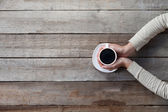 Woman hands holding mug of hot coffe