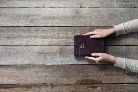 Woman hands on bible