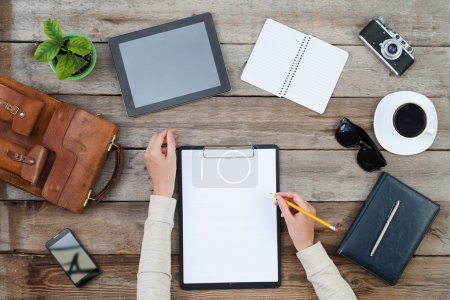 Woman's hand writing on paper with ipad style tablet and other items around