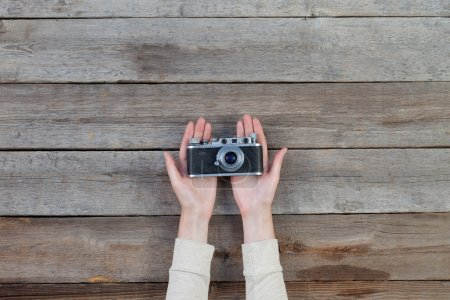 Hand holding a retro camera over wooden table