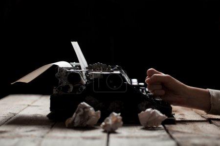 Photo pour Mains écrivant sur la vieille machine à écrire sur fond de table en bois - image libre de droit