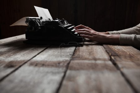 Photo for Hands writing on old typewriter over wooden table background - Royalty Free Image