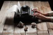 Hands writing on old typewriter over wooden table background