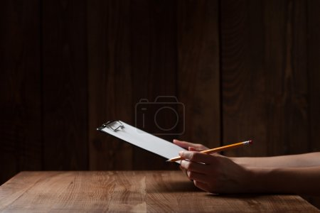Closeup of woman's hand writing on paper over wooden table