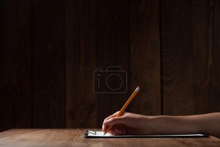 woman's hand writing on paper over wooden table