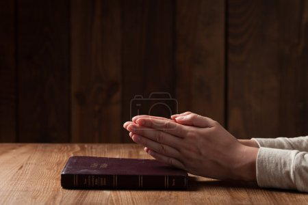 woman hands on bible. she is reading and praying over bible over