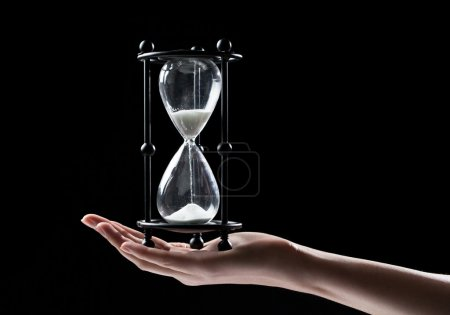 Photo for Hand holding a sand watch hourglass over black background - Royalty Free Image