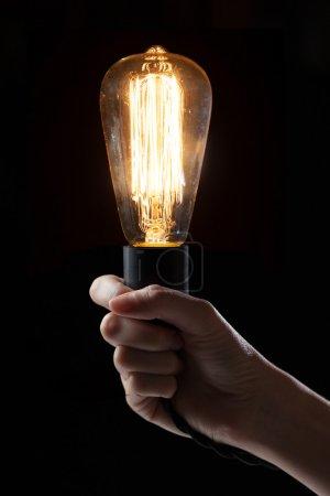 Hand holding classic Edison light bulb