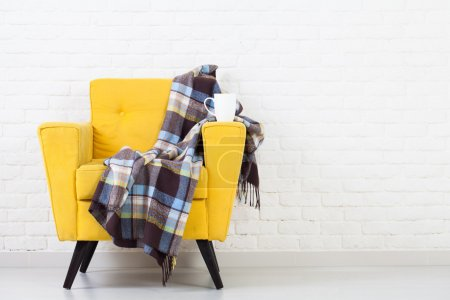 White wall texture with a retro yellow armchair