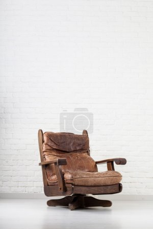 Leather retro armchair next to a wall