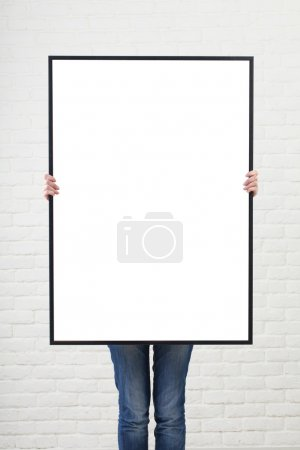 Photo for Woman with blank poster on wall background - Royalty Free Image