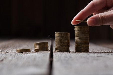 Hand putting coins to a stack on a wooden background