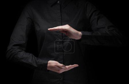 Photo pour Concept de dvertisement / gros plan de femmes mains coupées montrant quelque chose sur fond noir - image libre de droit