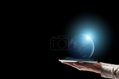 Computer tablet with a hand touching a touchscreen and Earth