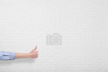 Foto de Mano con pulgar hacia arriba aislado sobre fondo de pared de ladrillo blanco - Imagen libre de derechos