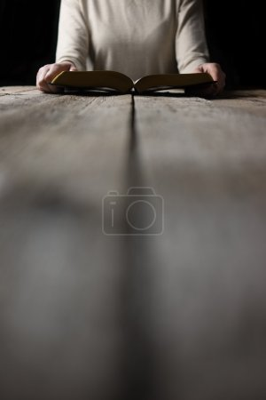 Woman hands on bible. she is reading and praying over bible in a