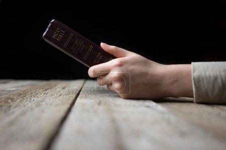 Photo pour Femme les mains sur la bible. elle est la lecture et prier au cours de la bible sur la table en bois - image libre de droit