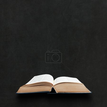 Photo for Opened book on a blackboard background - Royalty Free Image