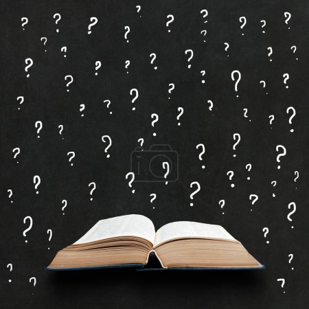 Opened book on a blackboard background with aquestion marks