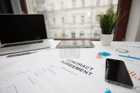 contract document on a table surrounded by a laptop and a smart