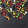 Top view on colorful toy cars over blackboard back...