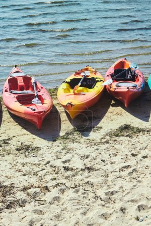 Kayaks in red and yellow colours on a beach