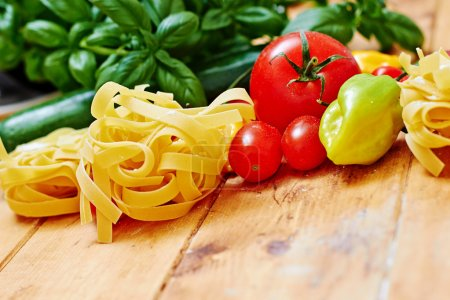 Photo for Raw tagliatelle with vegetables on  wooden table, colour and space - Royalty Free Image
