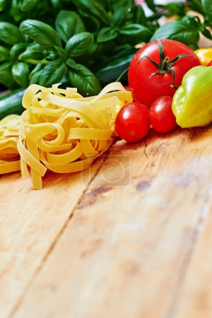 Raw tagliatelle with vegetables on  wooden table