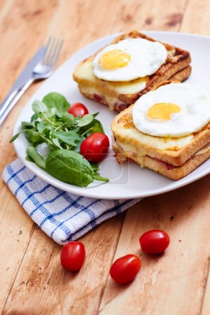 Croque madame with salad on wooden table