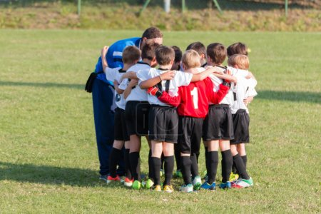 Little league players together in huddle, teamwork strategy to w