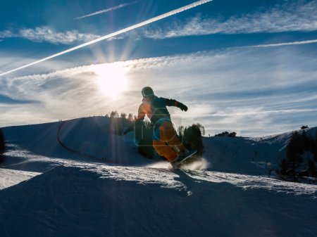 Freestyle snowboarder with helmet in snowpark, silhouette