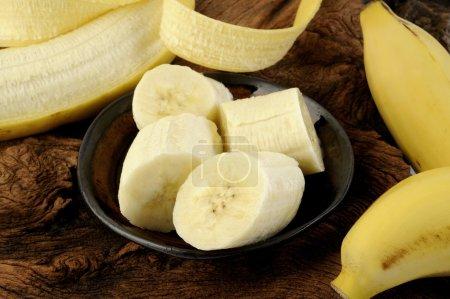 Foto de Rebanadas de plátano en tazón sobre fondo de madera - Imagen libre de derechos