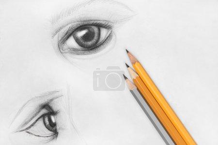 Photo pour Trois crayons et papier avec croquis dessus - image libre de droit